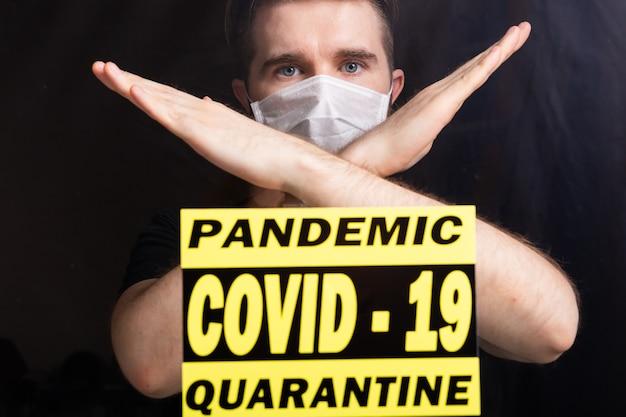 Homem com máscara respiratória, mostrando o gesto de parada. guy mostrar gesto não. pare o coronavírus ou covid-19 e a pandemia