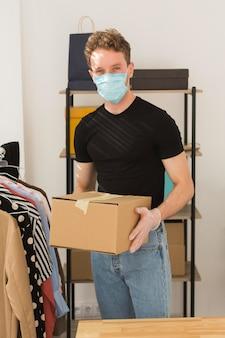 Homem com máscara segurando a caixa