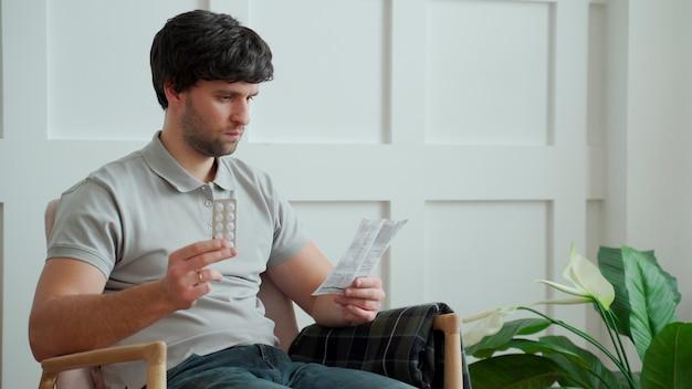 Homem com medicamentos lê as instruções de uso médico do medicamento.