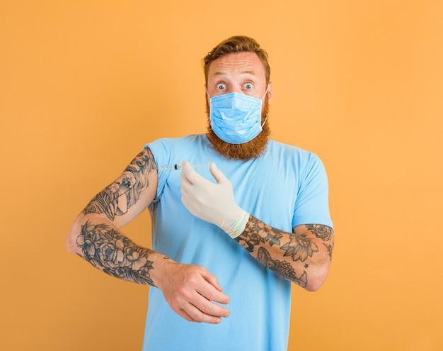 Homem com medo de barba, tatuagem e máscara para covid-19 está pronto para a vacina contra o vírus