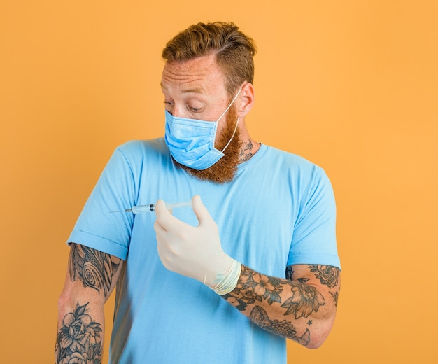 Homem com medo de tatuagem de barba e máscara para cobiça está pronto para a vacina contra o vírus