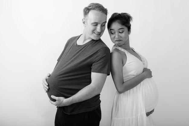 Homem com melancia como estômago e mulher asiática grávida juntos como casal multiétnico em preto e branco