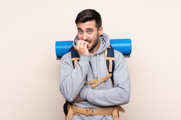 Homem com mochila alpinista sobre parede isolada