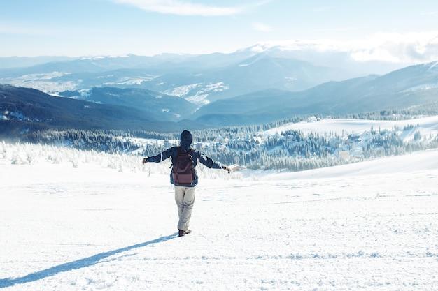 Homem com mochila, caminhadas nas montanhas. tempo frio, neve nas colinas. caminhadas de inverno. o inverno está chegando, primeira neve. conceito de viagem, descanso, relaxamento
