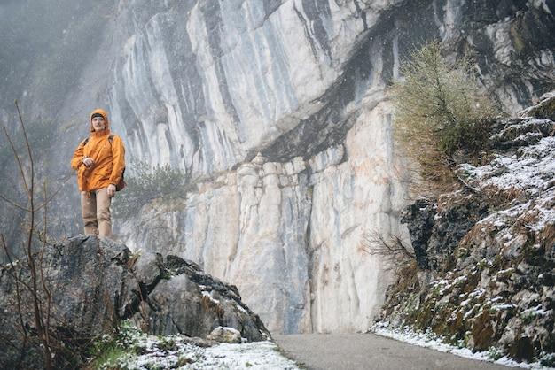 Homem com mochila caminhando em montanhas rochosas com neblina