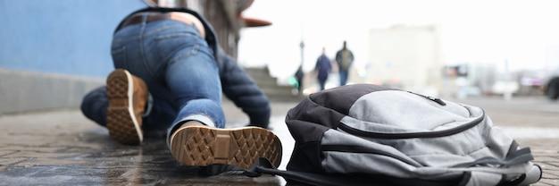 Homem com mochila deitado na calçada escorregadia após o outono, close up