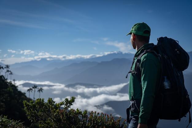 Homem com mochila, olhando a vista para a montanha. conceito de viagens e aventura. foto de alta qualidade