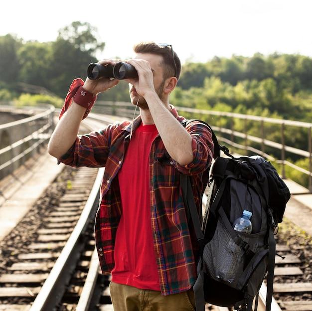 Homem com mochila, olhando com binóculo