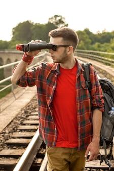 Homem com mochila, olhando com o binóculo em distância