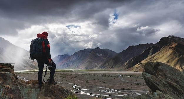 Homem com mochila segurando a câmera em pé na falésia com vista para montanhas e a luz do sol através da nuvem.