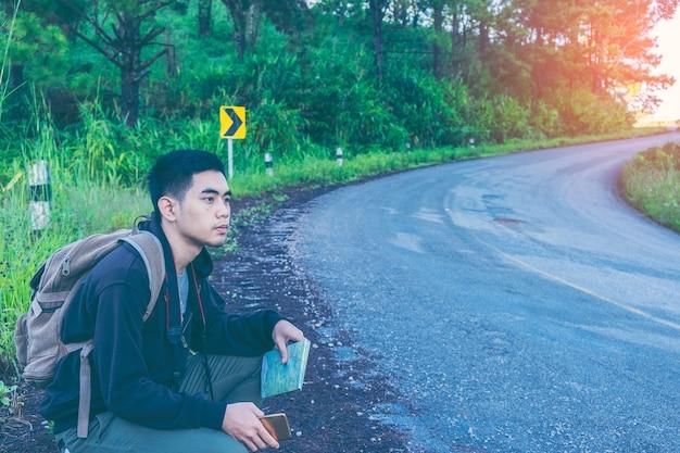 Homem com mochilas em roupas de viagem casual andando pela estrada, caminhadas na estrada. viajante sentado na rodovia engatando