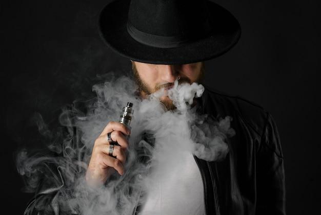 Homem com modificação vaping que exala o vapor no estúdio preto. cara barbudo fumando cigarro para parar de fumar. conceito de fumo livre de vapor e alternativa à nicotina