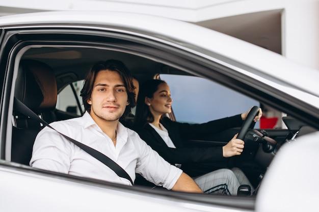 Homem com mulher em uma sala de exposições, escolhendo um carro