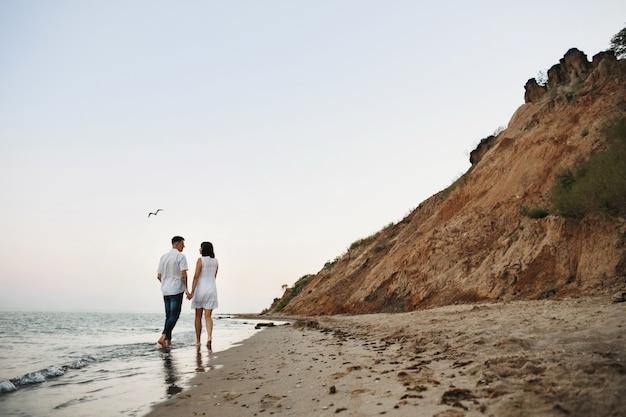 Homem com mulher está caminhando ao longo do mar