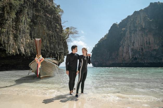 Homem com mulher nos braços na praia de phi phi, aproveitando as férias de verão lindas.