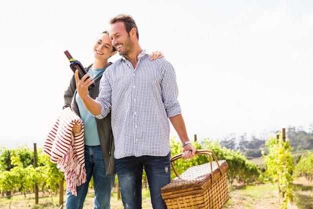 Homem com mulher segurando cesta e garrafa de vinho