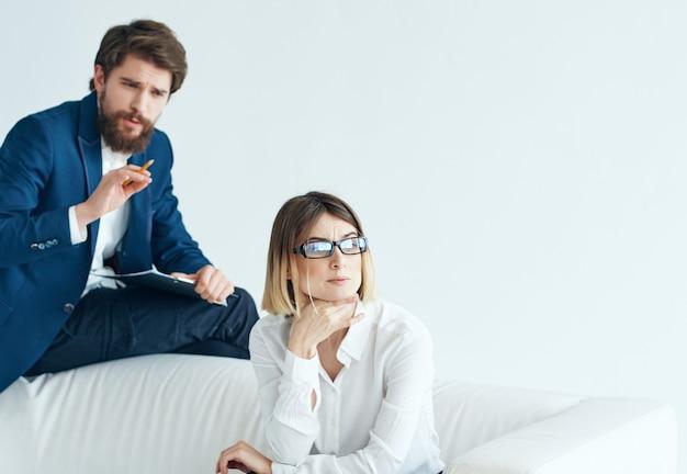 Homem com mulher sentada em um sofá branco comunicação equipe trabalho de escritório