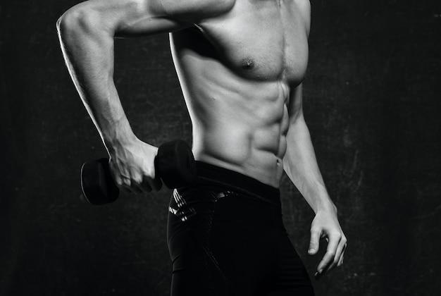 Homem com músculos do tronco inflado, halteres, ginástica
