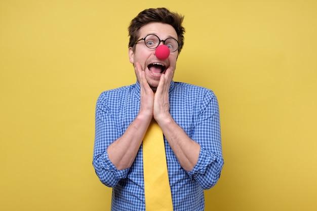 Homem com nariz de palhaço vermelho e gravata amarela sendo chocado. dia da mentira no dia primeiro de abril