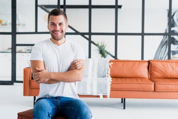 Homem com o braço cruzado e sentado em um banquinho