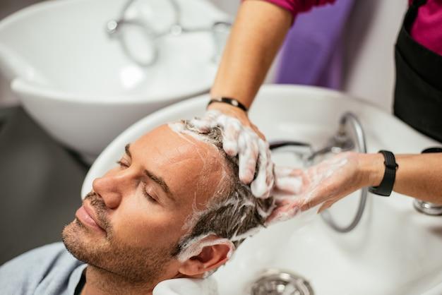Homem com o cabelo lavado em uma barbearia