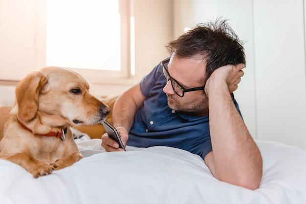 Homem com o cachorro usando telefone inteligente na cama
