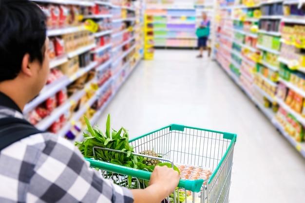 Homem com o carrinho de compras que compra o alimento em um supermercado. detalhe do close up de carrinho de compras.
