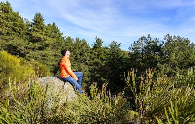 Homem com o rosto voltado para o sol nas montanhas, sentado em uma rocha, em uma manhã fria de primavera.