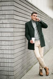 Homem com o telefone na jaqueta