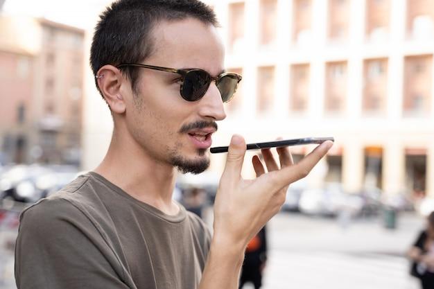 Homem com óculos de sol, falando no alto-falante do telefone móvel no meio da rua