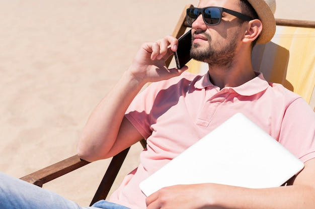 Homem com óculos de sol na praia com laptop e smartphone