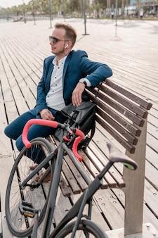 Homem com óculos de sol sentado em um banco ao lado de sua bicicleta
