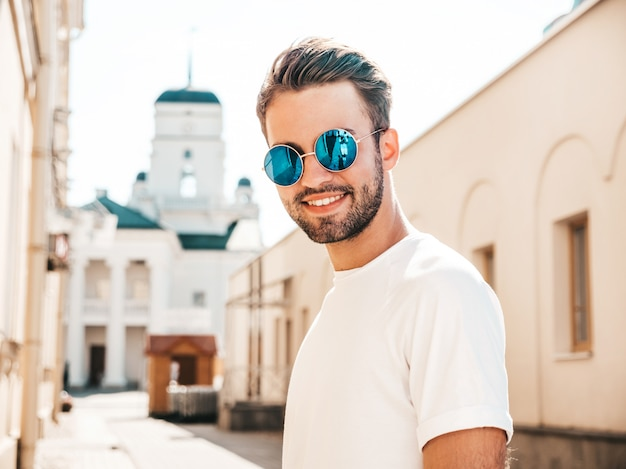 Homem com óculos de sol, vestindo camiseta branca posando
