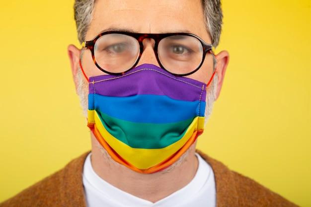 Homem com óculos embaçados pela máscara com a bandeira do orgulho gay