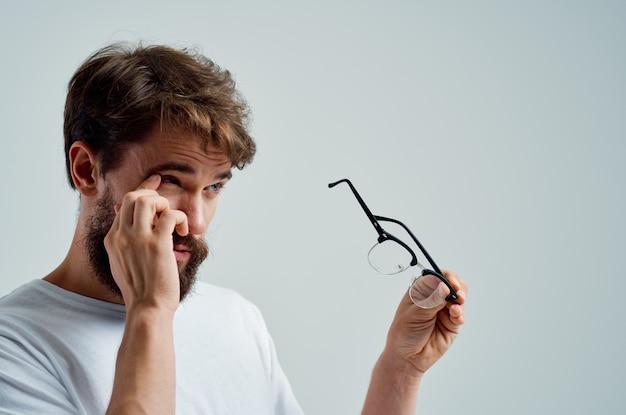 Homem com óculos na mão, close-up de problemas de visão