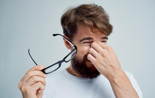 Homem com óculos na mão problemas de visão luz de fundo
