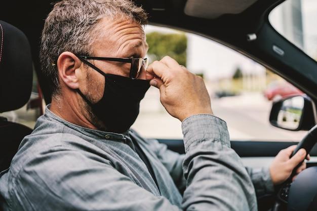 Homem com óculos, sentado em seu carro e colocando máscara protetora durante o vírus corona.