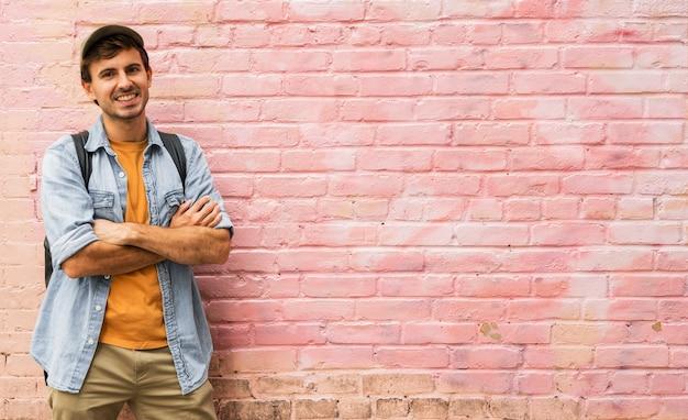 Homem com os braços cruzados com fundo rosa