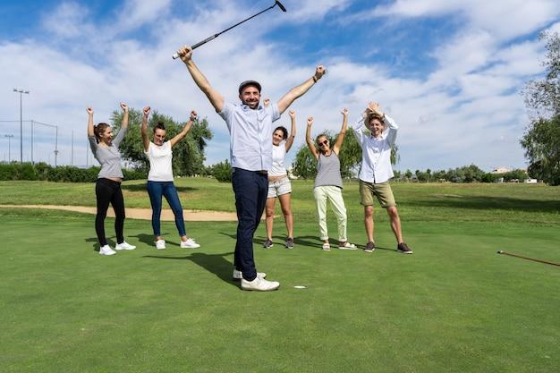 Homem com os braços levantados em uma expressão vitoriosa na frente de um grupo de pessoas que estão comemorando em um campo de golfe