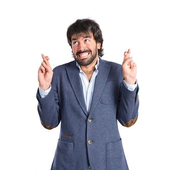 Homem com os dedos cruzados sobre fundo branco