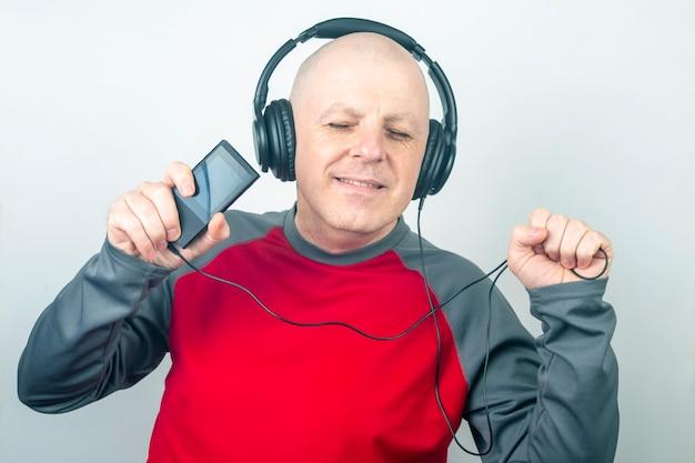 Homem com os olhos fechados ouve música com fones de ouvido em um fundo claro
