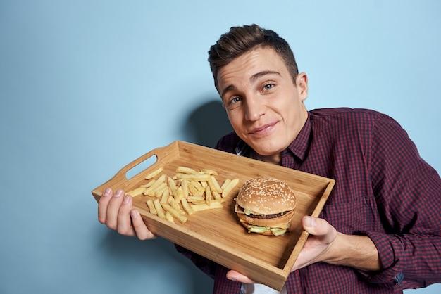 Homem com palete de madeira, fast-food, hambúrguer de batatas fritas
