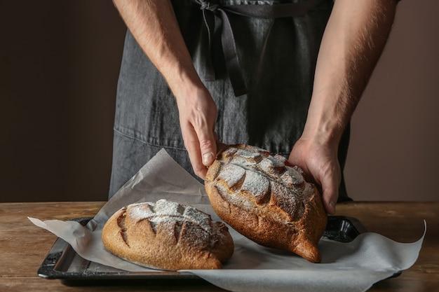 Homem com pão acabado de cozer na mesa, closeup
