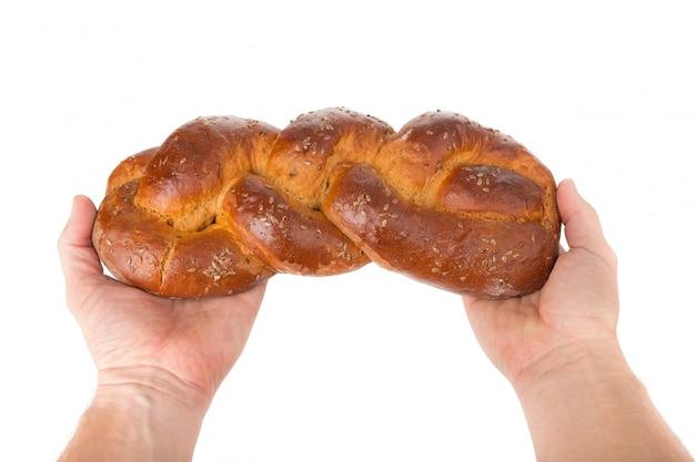 Homem com pão nas mãos como bem-vindo. feche na parede branca.