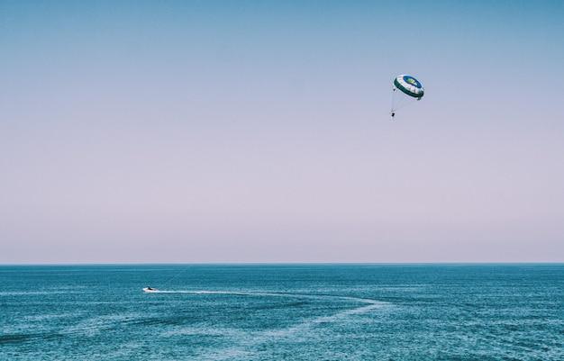 Homem com parashute à beira-mar