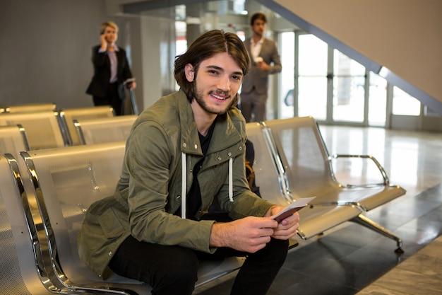 Homem com passaporte e cartão de embarque, sentado na sala de espera