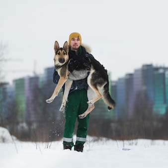 Homem com pastor alemão no parque no inverno