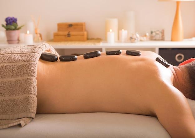 Homem com pedras na mesa de massagem no spa com tratamento corporal. pessoa mentindo e relaxando durante