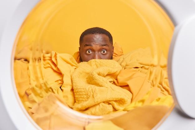 Homem com pele escura coberta com uma pilha de roupas sujas poses de dentro da máquina de lavar lavando roupas sujas em poses caseiras