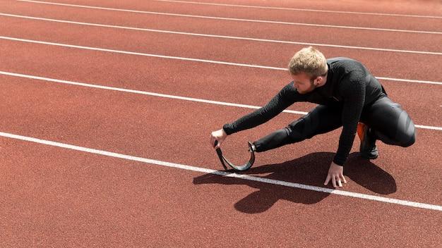Homem com perna protética alongando-se em tiro completo